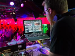 Guy DJ'ing in a club with laptop